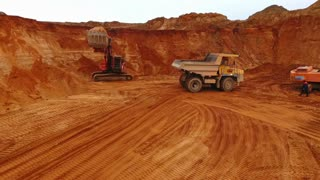 Mining machinery working at sand quarry. Mining truck moving backwards at sand mine. Dumper truck working at sand quarry. Industrial machinery on sand quarry. Dump truck. Mining industry