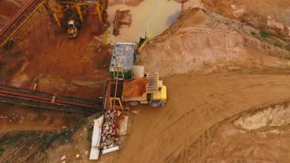 Mining truck transporting sand to sorting conveyor belt. Mining machinery in industrial area at sand quarry. Mining equipment. Mining industry. Dump truck. Heavy vehicle