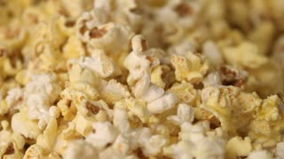 Mixing hot popcorn in heap. Close up of fresh popcorn flakes. Popping up pop corn. Process of popcorn production in slow motion. Cinema food concept. Pop corn background