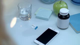 Mobile reminder time to taking medicine. Close up of mobile phone and female hand taking drugs. Daily dose of medicaments. Mobile time take pills