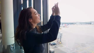 Modern girl taking film on phone departure of plane at airport throught window in slow motion. Young woman make video with her smartphone