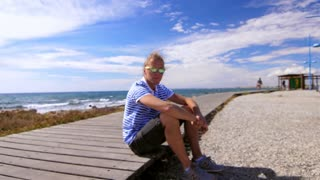 Modern guy in sunglasses gently smiling on seashore in slow motion. Stylish man sitting at sea coast. Hipster man relaxing on ocean beach. Enjoying summer holidays