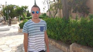 Modern man in sunglasses walking in tropical city. Stylish man in sun glasses enjoy summer walk. Male tourist walking on resort. Hipster man in sunglasses enjoy summer trip