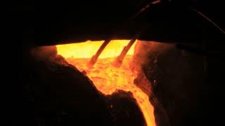 Molten metal start pouring from blast furnace. Metallurgical industry. Liquid metal in metal furnace. Liquid metal production process. Molten steel flow from steel furnace