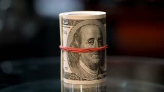 Money roll on table. Roll of hundred dollar bills knitted by red rubber band on table. Credit proposition from bank. Investment financial operations. Business success and financial grow