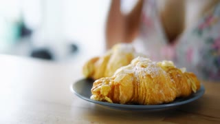 Morning breakfast with delicious pastry. Traditional brunch with coffee and french croissants. Close up woman hand taking freshly croissants from plate. Croissant and coffee macro view