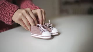 Mother hands playing with knitted baby booties. Close up pink knitted booties for newborn in female hands. Knitted clothes for children. Expecting baby concept