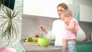 Mother holding baby on hands in kitchen. Woman cooking fresh salad with child on hands. Mom prepare dinner with kid. Woman preparing food with daughter. Young mother cooking food with toddler girl