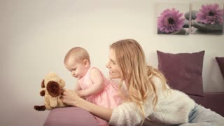 Mother playing with baby. Beautiful baby playing with toy on bed. Happy mothers day. Mom enjoy time with child. Sweet child looking toy dog