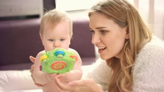 Mother playing with baby. Beauty girl play with baby rattle. Young mother enjoy time with daughter. Mom have fun with infant. Happy childhood