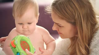 Mother playing with child. Close up of woman show green baby rattle to her daugther. Naked baby girl learning play. Sweet child sitting with mom. Infant playing with toy