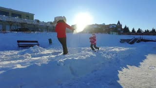 Mother playing with little daughter on snow. Winter family fun in slow motion. Snow holiday family concept. Happy wintertime. Winter snow games