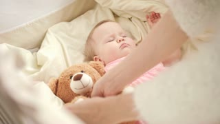 Mother putting toy to sleeping baby in cot. Beautiful child girl sleeping with toy bear. Sweet bed time for kid. Portrait of adorable baby sleep in crib. Dream time for little girl