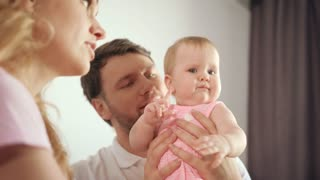 Mother shaking head for baby. Happy family together playing with baby girl. Smiling parents enjoy parenthood. Sweet family love concept. Cute infant in father hand smile to mom. Joyful family have fun