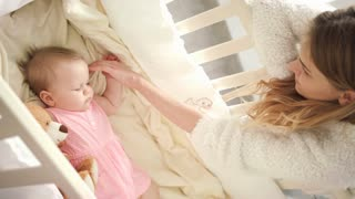 Mother stroking sleeping baby. Beautiful motherhood. Cute infant sleeping in crib. Mom standing near cot. Mother care baby in bed. Sweet dream time. Child resting in white bed. Adorable childhood