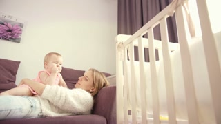 Mother with baby lying on sofa. Pretty woman lying on bed with kid. Mom hugging little child. Beautiful toddler with mother in baby room. Family lifestyle concept