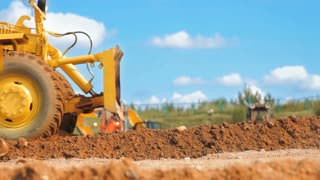 Motor grader leveling ground. Close up of construction machinery. Earth moving equipment working on construction site. Heavy earthmover technics working