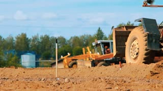 Motor grader leveling ground on construction site. Heavy machinery working in sand quarry. Close up mining industry worker going on camera. Excavation building territory for new construction