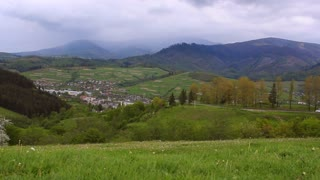 Mountain village landscape. View of the village located in the mountains. Road in mountains. Panorama with village and road among hills. Mountain town in green hills
