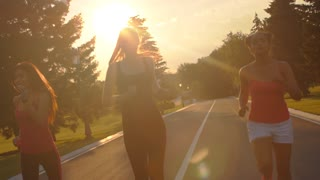 Multi ethnic women running in park at sunset. Authentic women group running in slow motion. Close up of running women at sunset. Fitness training outdoor. Multiethnic runners at sunset