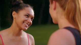 Multi racial girlfriends talking in summer park. Closeup of multi ethnic girls talking. Close up of female friends laughing outdoor. Diverse people outdoor. Multiethnic girlfriends talking outdoors