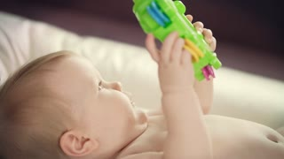 Naked baby lying with toy. Close up of female hands change diaper. Mother care. Infant hygiene concept