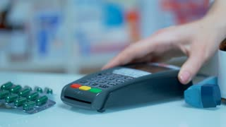 Nfc payment at drugstore. Close up of male hand using mobile payment at nfc terminal. Customer payment drugs with nfc technology. Medical payment with mobile pay