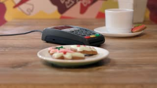 NFC payment technology. Customer paying by contactless credit card over pos terminal in cafe. Female hand paying cockies by credit card with nfc chip. Wireless money transaction in cafe