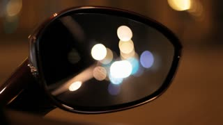 Night city in car rear view mirror. Night reflection of street lights. Side mirror rear view from moving auto at night. Car mirror. Automobile mirror