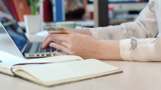 Online payment solutions. Woman hands holding credit card and using laptop for online shopping in office. Digital wallet and online banking. Female hands using digital payment