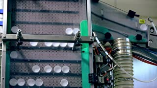 Packaging industry manufacturing machine. Bottle caps for packaging on automated conveyor belt. Plastic bottles caps on manufacturing line. Packaging manufacturing equipment