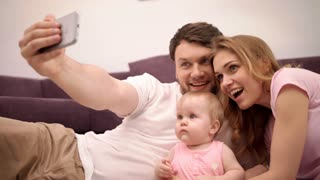 Parents kissing baby. Happy family taking selfie photo at home. Smiling man take selfie on smartphone with wife and child. Young family happiness at home. Joyful family photo on mobile phone