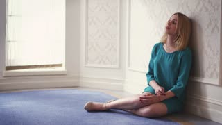 Pensive woman sitting on floor leaning on wall in light room. Thoughtful woman sitting on carpet floor and leaning on wall nearly window. Attractive girl dreaming