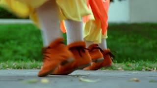 People dancing foots in orange Irish national clothing. Closeup of feets dancing Irish national dance. Folklore dancers background. National entertainment