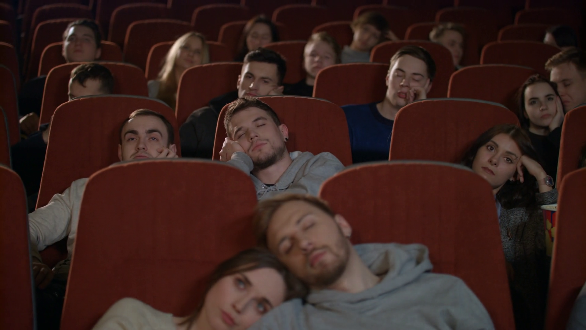 People watch boring movie at cinema in slow motion. Group of young people  sleeping watching boring movie in cinema. Bored audience watching film in  cinema. Spectators fall asleep from boring film Stock