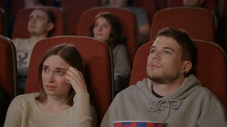 People watching scary film in movie theater. Young man sprinkling popcorn. Shocked girl covering face with hands in cinema. Spectators frightened by horror film. Scared people watching horror