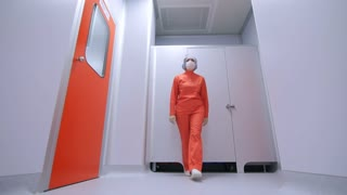 Pharmaceutical factory worker go in sterile corridor. Pharmaceutical worker in face mask walking white corridor. Female scientist in orange uniform moving in laboratory corridor
