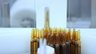 Pharmaceutical manufacturing at pharmacy factory. Close up of yellow medical ampoules on conveyor line. Medicine packaging line. Medicine bottles at automated production line