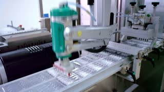Pharmaceutical manufacturing line. Automated production line. Medicine industry. Industrial equipment at pharmaceutical plant. Packaging machine. Medical ampoules on conveyor line at drug factory