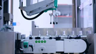 Pharmaceutical manufacturing line. Robotic arm at pharmaceutical plant. Pharmacy factory conveyor belt. Pharmaceutical production line. Packaging machine. Medicine industry. Automated process