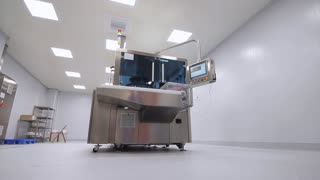 Pharmaceutical worker approach to pharmaceutical equipment in pharmacy factory. Medicine production machine at pharmaceutical plant. Pharma manufacturing machinery