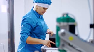 Pharmaceutical worker at pharmaceutical manufacturing line. Factory worker on pharmacy production line. Pharmaceutical factory. Woman working at pharmaceutical plant. Packaging line at drug factory