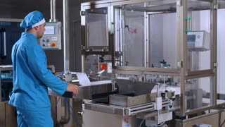 Pharmaceutical worker operate computer equipment at pharmaceutical plant. Packaging machine at pharmaceutical factory. Operator control pharmaceutical manufacturing line. Drug production