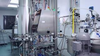 Pharmacist control pharmaceutical equipment at modern factory. Pharmaceutical worker controlling manufacturing line. Pharmaceutical industry. Pharmaceutical manufacturing factory interior
