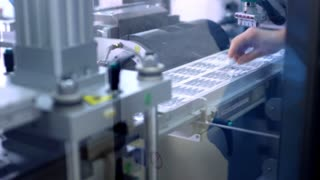 Pharmacy industry. Pharmaceutical packaging line. Pharmaceutical worker puts medical vial on production line. Pharmacy production process. Pharmaceutical manufacturing. Vial medical production line