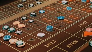 Player betting on gambling table. Casino roulette table brown surface with classic betting grid. Close up man hand puts down casino chips on table. Gambling game in traditional casino