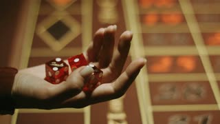 Player hand throwing red dices on gambling table. Close up woman hand holding three dices. Gambling game in craps at casino. Gambling addiction concept