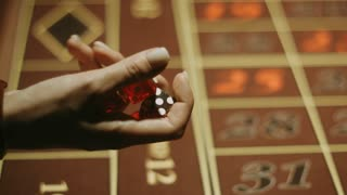 Player with red dices near gambling table. Close up woman hand holding three dices. Game of chance in casino. People playing in craps game. Gambling addiction problem