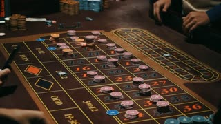 Players hands betting on roulette table. Casino gambling table brown surface with classic betting grid. Close up human hand puts down casino chips on sectors with numbers. Gambling game in casino