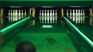 Playing bowling game on colorful alley. Bowling ball knocks down 7 pins. Process of bowling game. Bowling strike competition. Colorful Illumination. Ball is rolling on playing field